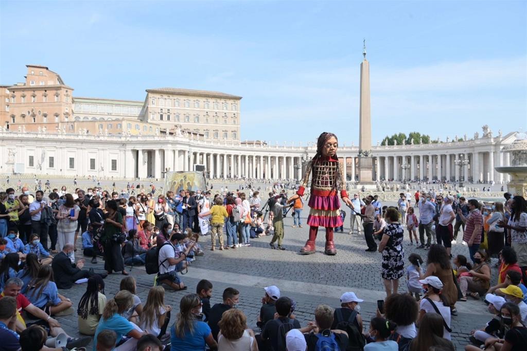 """La piccola Amal è un burattino alto 3,5 metri che raffigura una giovane rifugiata di circa 9 anni. Rappresenta idealmente tutti i bambini sfollati, molti dei quali separati dai loro genitori. Ha percorso oltre 8.000 km in cerca della sua famiglia per incarnare il monito: """"Non dimenticatevi di noi"""". - Siciliani"""