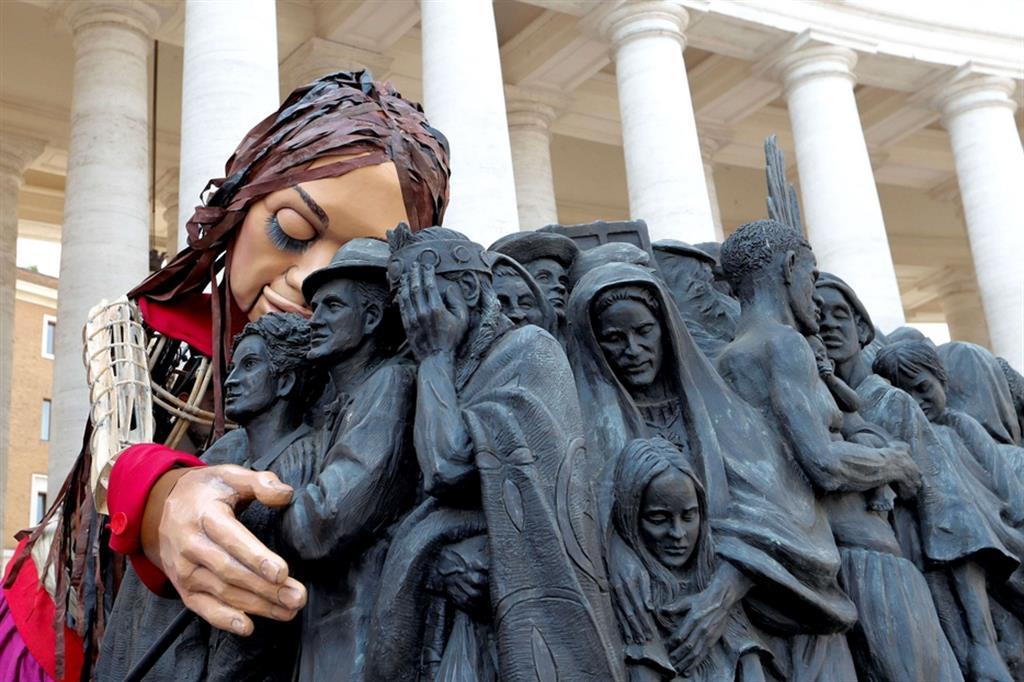 """L'abbraccio di Amal alla statua """"Angel Unawares"""". Realizzata a grandezza naturale raffigura un gruppo di migranti e rifugiati, provenienti da diversi contesti culturali e razziali e anche da diversi periodi storici. Sono messi vicini, stretti, spalla a spalla, in piedi su una zattera, coi volti segnati dal dramma della fuga, del pericolo, del futuro incerto. All'interno di questa folla eterogenea di persone, spiccano al centro le ali di un angelo, come a suggerire la presenza del sacro tra di loro. - Reuters"""