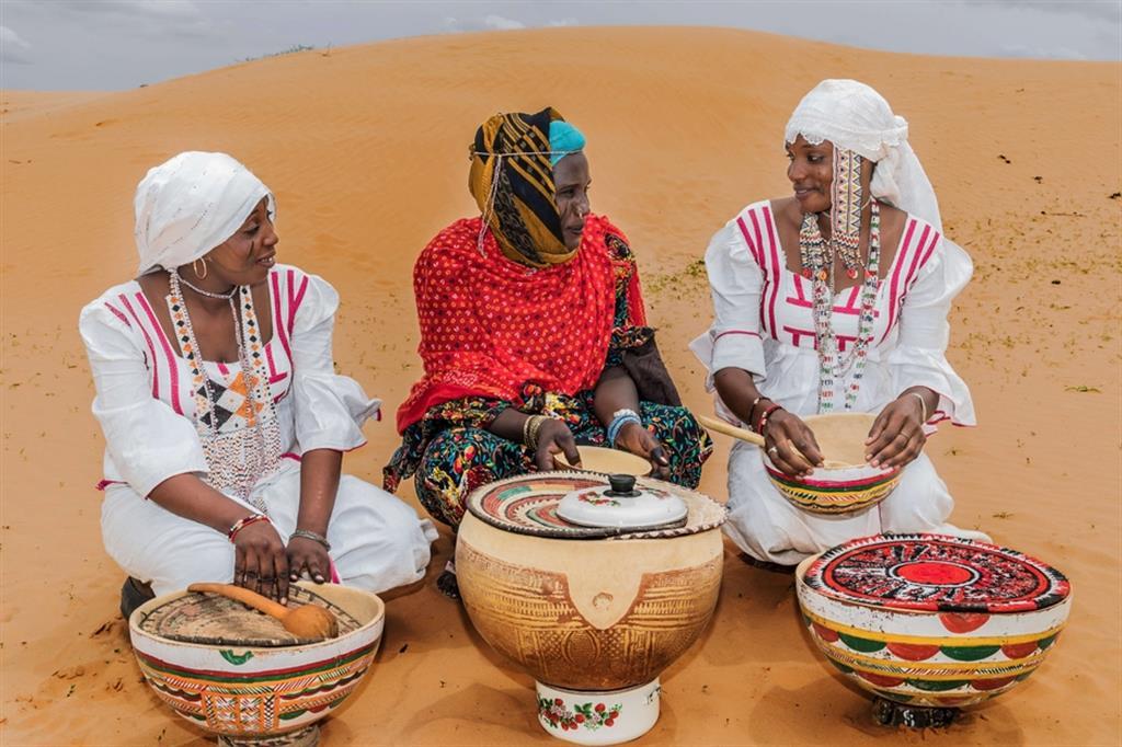 B.M., 24 anni, di etnia Peulh, sfollata di Tam, commerciante di latte vaccino; H.O., 33 anni, Peulh, rifugiata di Kanamma (Nigeria), commerciante di latte vaccino; R.A., 22 anni, Peulh, sfollata di Tam, commerciante di latte vaccino e polpette di miglio. Nella foto, si osservano le donne mentre utilizzano gli utensili da cucina tradizionali in legno e ceramica tramandati di madre in figlia attraverso il corredo matrimionale. - ApsatouBagaya/COOPI