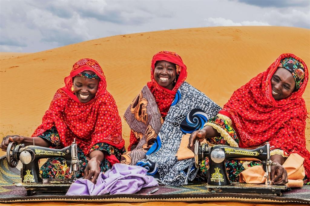 """F.T., 26 anni, di etnia Kanouri, rifugiata di Kanamma (Nigeria), sarta; M.A., 30 anni, Kanouri, sfollata di Tam, commerciante di tessuti; A.M., 35 anni, Kanouri, sfollata di Tam, sarta. Tutte  beneficiarie delle Attività Generatrici di Reddito (AGR) del progetto. Nella foto, si osservano le donne intente a cucire il """"pagne"""" (tessuto tipico africano) utilizzando macchine da cucire manuali, mentre sono sedute su una stuoia in vimini anch'essa tradizionale del Niger. In Niger, tutte le donne richiedono ai sarti e sarte locali di confezionare i loro vestiti. Si tratta quindi di un'attività molto importante, tanto che un noto stilista nigerino, Alphadi, è conosciuto in tutto il mondo - ApsatouBagaya/COOPI"""