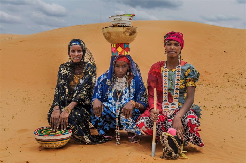 M.A., 35 anni, di etnia Peulh, sfollata di Tam, vende latte vaccino e polpette di miglio; F.A., 33 anni, Peulh, sfollata di Tam, vende latte vaccino; Z.H., 25 anni, Peulh, sfollata di Tam, alleva bestiame. Tutte sono beneficiarie delle Attività Generatrici di Reddito (AGR) del progetto. Sono donne Peulhs che amano vestirsi come le donne kanouri, ma si differenziano per le cicatrici e gli ornamenti. Le donne di etnia peulh, nomadi e allevatrici, portano sempre con sé un bastone, utilizzato per guidare il bestiame, e una borraccia, coperta con un panno spesso per mantenere l'acqua alla giusta temperatura. Le donne trasportano sulla testa le « calabasses » dove viene conservato il latte bevuto dalla famiglia. - ApsatouBagaya/COOPI