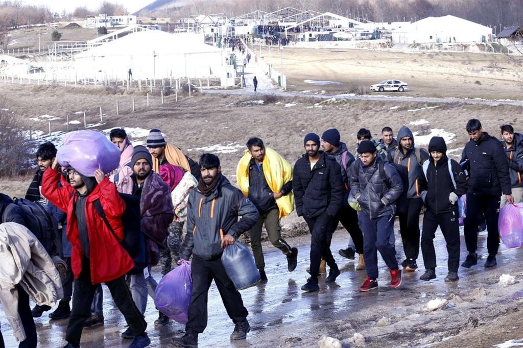 Migranti che si allontanano dal campo profughi di Lipa, distrutto da un incendio