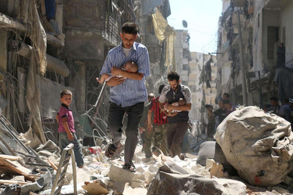 Padri - Due uomini, in una pausa di uno dei quotidiani bombardamenti, portano in salvo i bimbi neonati nel quartiere di Salihin nella periferia settentrionale di Aleppo: l'assedio alla città è divenuto simbolo della guerra in Siria - Ansa