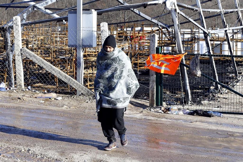 Un uomo davanti a quel che resta del campo di Lipa, bruciato nell'incendio del 23 dicembre - Ansa
