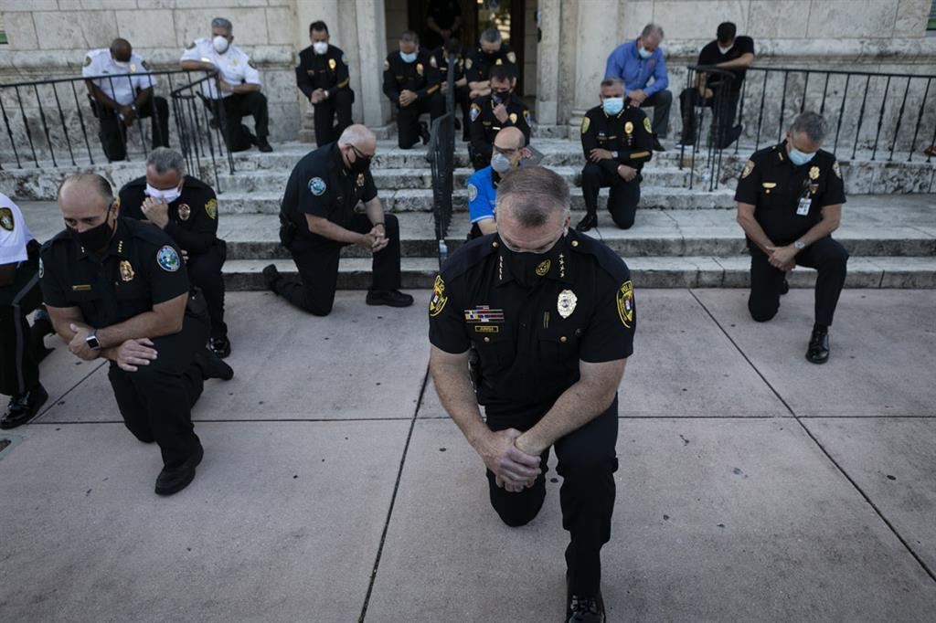 Gli agenti di polizia si inginocchiano durante una manifestazione a Coral Gables, in Florida, il 30 maggio 2020 in risposta alla recente morte di George Floyd, un uomo di colore disarmato morto mentre veniva arrestato e bloccato a terra da un agente di polizia di Minneapolis. Sono scoppiati scontri e le principali città hanno imposto il coprifuoco mentre l'America iniziava un'altra notte di disordini sabato con manifestanti arrabbiati che ignoravano gli avvertimenti del presidente Donald Trump che il suo governo avrebbe fermato le violente proteste contro la brutalità della polizia. (Eva Marie UZCATEGUI / AFP _FFE21) - Eva Marie UZCATEGUI / AFP _FFE21