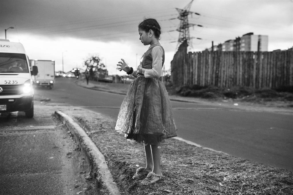 Una ragazzina guarda il bicchiere di plastica vuoto con cui chiede l'elemosina, lungo una strada della capitale Bogotà. Fino al giugno 2019, l'Istituto colombiano di assistenza familiare (ICBF) aveva fornito assistenza a quasi 80.000 bambini, adolescenti e famiglie venezuelane in tutto il paese. All'inizio del 2020, il governo colombiano ha annunciato due nuovi permessi di soggiorno speciali che avrebbero consentito a più di 100.000 venezuelani di rimanere e lavorare nel paese e ha inoltre stabilito che i bambini nati nel territorio nazionale da genitori venezuelani  possano acquisire la nazionalità colombiana.  Nel 2021 il governo ha poi deciso di garantire status legale a tutti i migranti venezuelani arrivati dopo il 2016. La misura ha permesso a 1 milione di persone di vivere e lavorare nel paese, potendo accedere ai servizi di assistenza sanitaria e istruzione. Tuttavia, un gran numero di persone continua a vivere in uno stato di forte povertà. Il diritto alle cure, all'istruzione e all'accesso al cibo sono spesso negati ai bambini. 31 ottobre 2018. Bogotà, Colombia. (Nicolò Filippo Rosso_World Report Award Master_FFE21) - Nicolò Filippo Rosso_World Report Award Master_FFE21