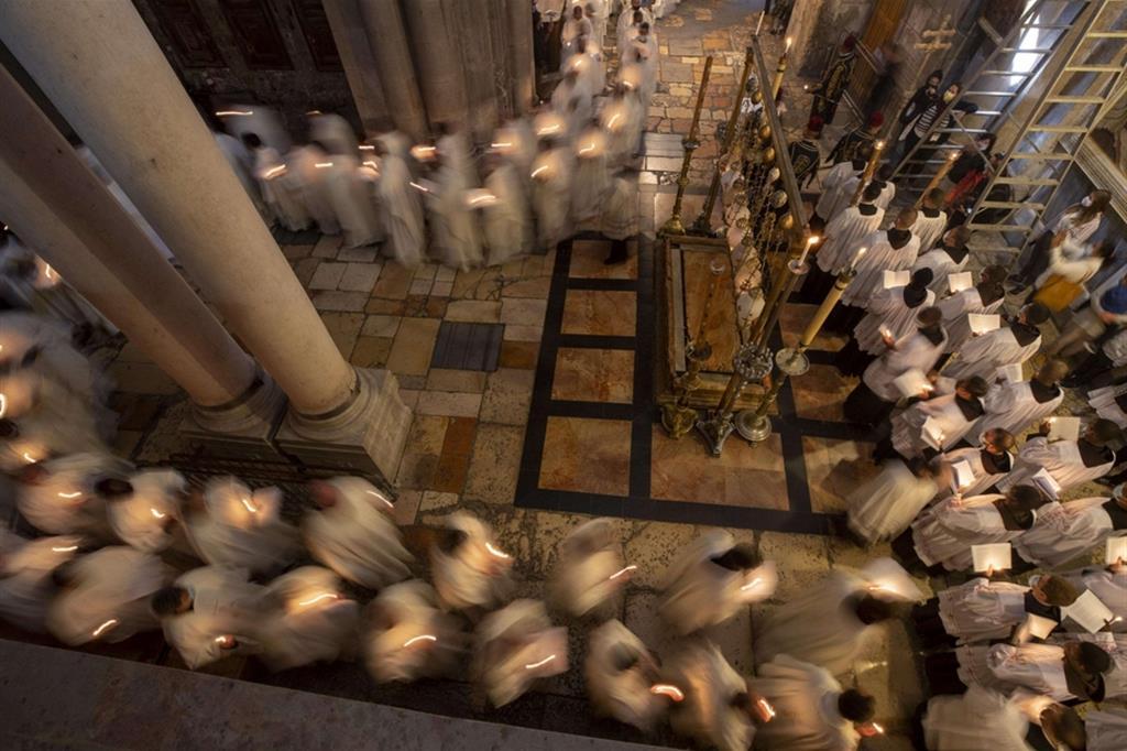 """La processione dei religiosi cristiani al Santo Sepolcro. In base alle regole dello """"Status quo"""", tutte le liturgie (compresa la Veglia pasquale) vengono celebrate alla mattina - Ansa"""